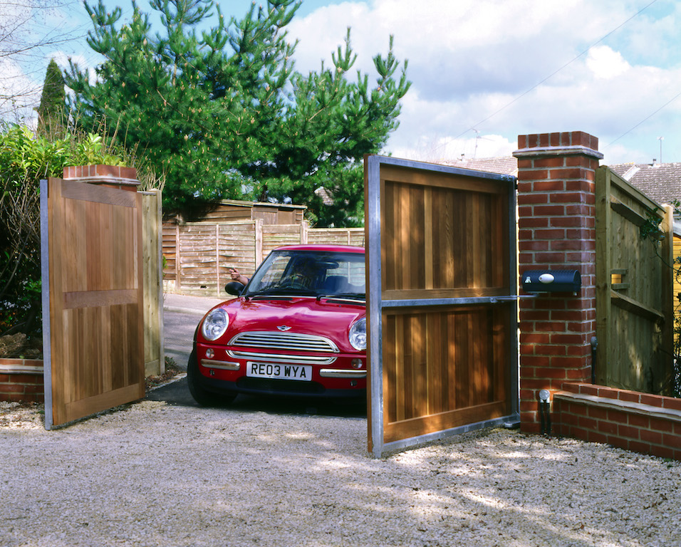 Red mini driver user timber automated gates in driveway